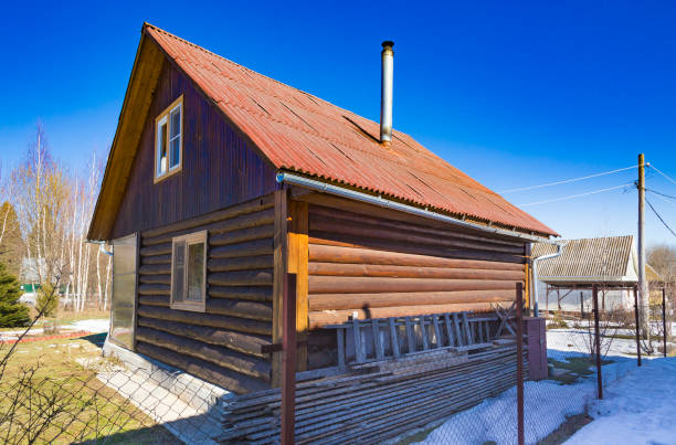 Typical Russian dacha made of wooden logs with chimney at blue sky background Perspective view at countryside cabin russian dacha stock pictures, royalty-free photos & images