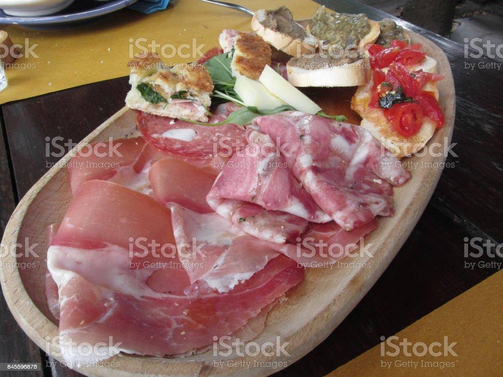 Typischen rustikalen toskanischen Vorspeise mit Crostini, Prosciutto, Brawn, Salami, Käse auf einem Holztablett. Italienische Vorspeise – Foto