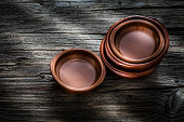 High angle view of typical spanish clay crockery arranged in a stack shot on rustic wooden table. Predominant color is brown. Low key DSRL studio photo taken with Canon EOS 5D Mk II and Canon EF 100mm f/2.8L Macro IS USM.