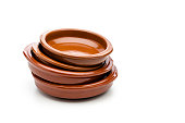 Typical spanish clay crockery stack isolated on white background. This crockery is mostly used for serving tapas like olives, peanuts, pickles, jalapeños and others in Spain bars and restaurants. High key DSRL studio photo taken with Canon EOS 5D Mk II and Canon EF 100mm f/2.8L Macro IS USM