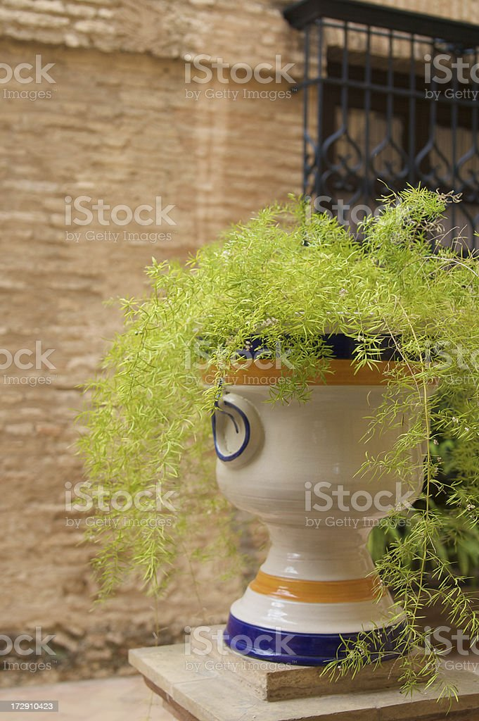 Typical Spanish Pot Against Brick Wall with Iron Work royalty-free stock photo