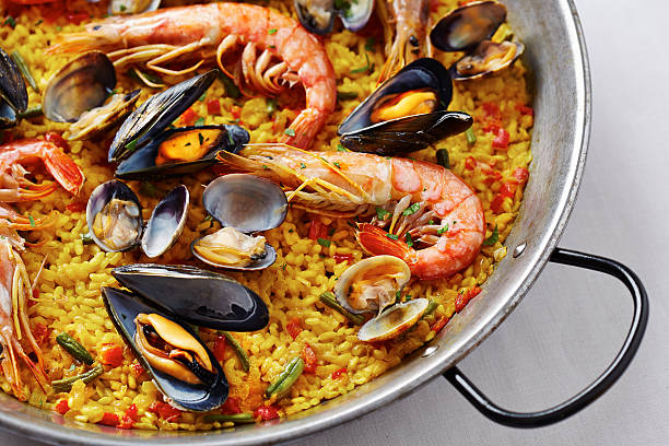 typical spanish seafood paella - paella stock photos and pictures