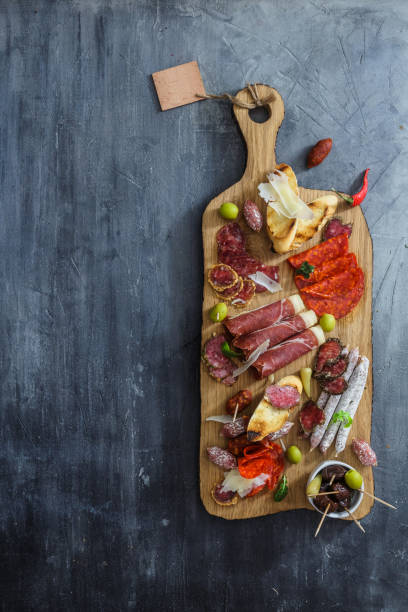 Typical spanish tapas concept. include variety slices jamon, chorizo, salami, bowls with olives, peppers. Copyspace. stock photo