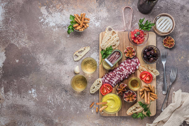 Typical spanish tapas concept. Salami, cheese, bowls with olives, tomatoes and alioli dip. Copyspace stock photo