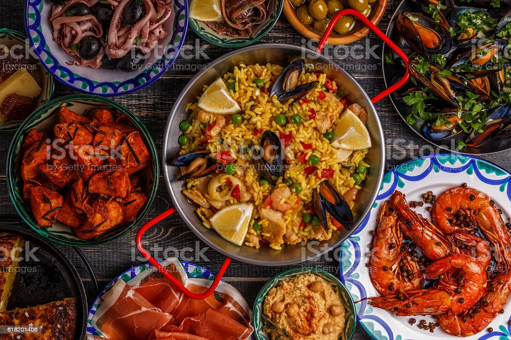 Typical spanish tapas concept, top view. Typical spanish tapas concept. Concept include slices jamon, bowls with olives,  anchovies, spicy potatoes, mashed chickpeas, shrimp, calamari, manchego with quince marmalade, pans with tortilla, paella, mussels  on a wooden table. Anchovy Stock Photo