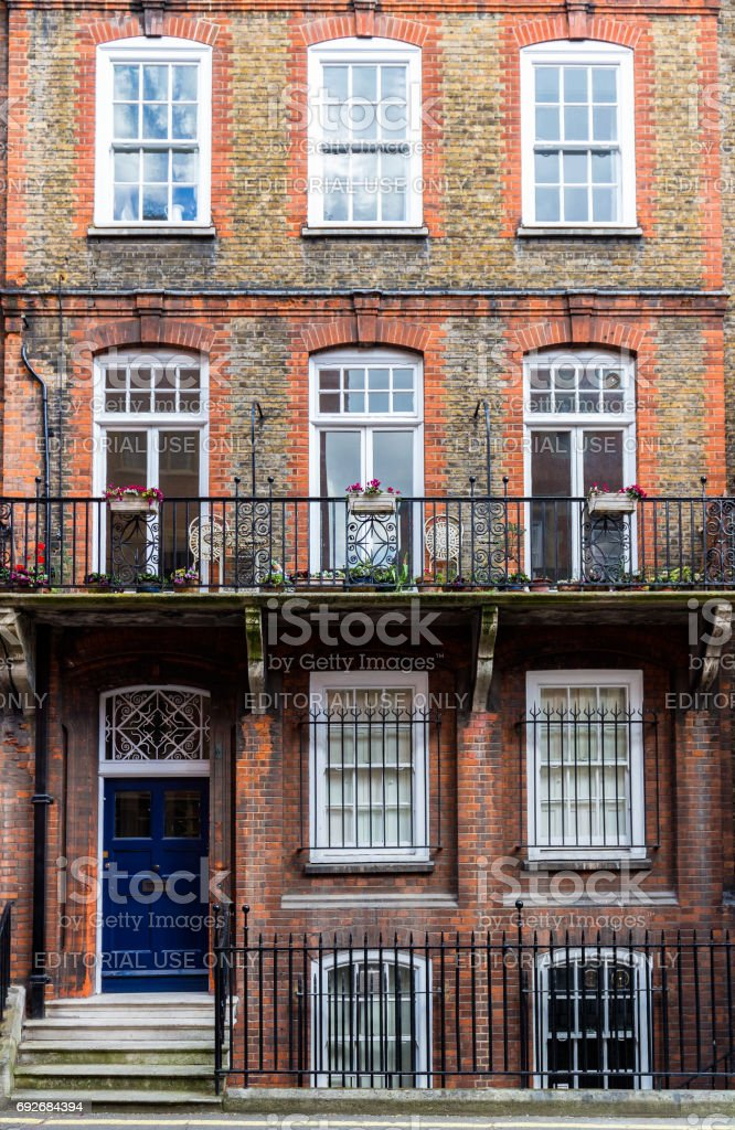 Typical street scene in the central London district with familiar architecture facades to urban housing. stock photo