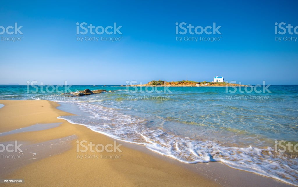 Typical summer image of an amazing pictorial view of a sandy beach with an old white church in a small island at the background, Malia, Crete, Greece. stock photo