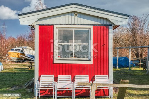 A typical Swedish red summerhouse with a square window and white chairs. The bare exterior has a simple aspect. Its wooden facade and the boats in the yard suggest it belongs to a local fisherman
