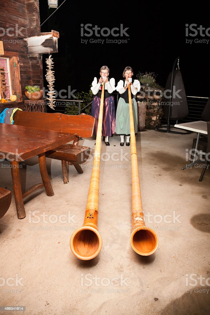 typical Swiss ladies play  Alpenhorn outside cafe stock photo