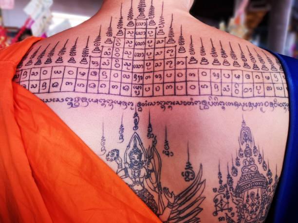 typische traditionelle thai religiöse tattoo auf rücken und schultern ein thailändischer buddhistischer mönch in einem nördlichen thai tempel in der provinz chiang mai in thailand. - buddhist tattoos stock-fotos und bilder