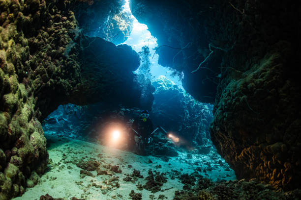 typical underwater cave in a red sea reef with an underwater photographer diver stock photo