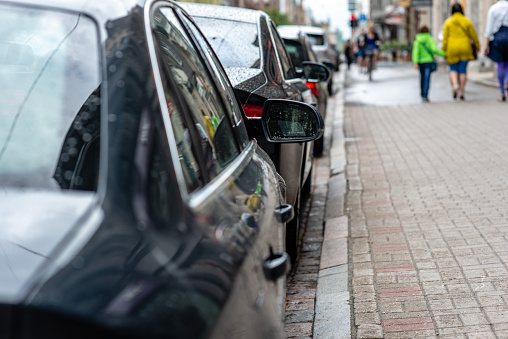 Typical urban landscape. Rear view of cars parked near the  street with soft-focus in the background - Image