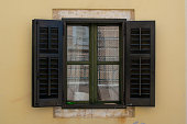 Typical window with wooden shutters in a yellow front wall in a typical croatian house in the old town of Porec, in Croatia