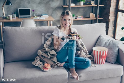 istock Typical woman weakness! Extremely happy woman is going to watch her favourite TV serials, eat donuts and popcorn on holiday 927875926