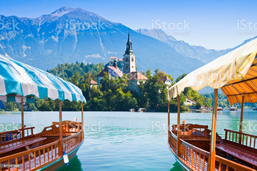 Typical wooden boats, in slovenian call 'Pletna', in the Lake Bled, the most famous lake in Slovenia with the island of the church (Europe - Slovenia) stock photo