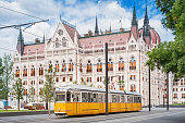 Stock photograph of a typical yellow tram passing beside the parliament building in Budapest, Hungary.
