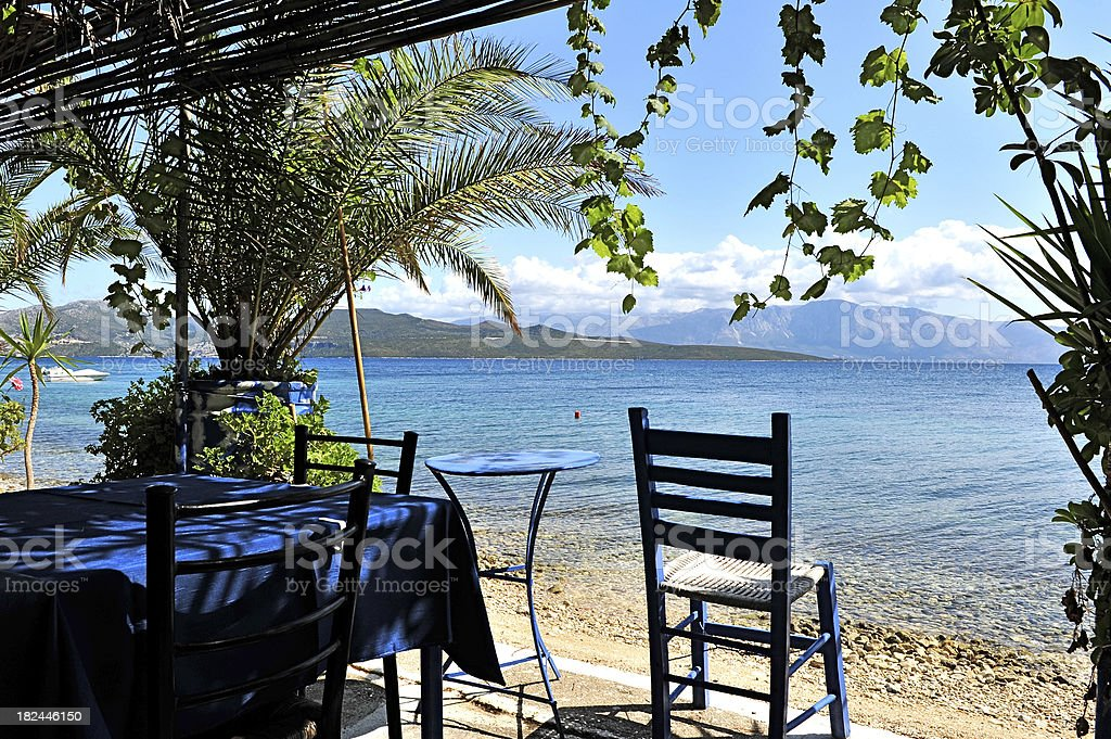 Typically Greek blue restaurant table and chairs in the shade royalty-free stock photo