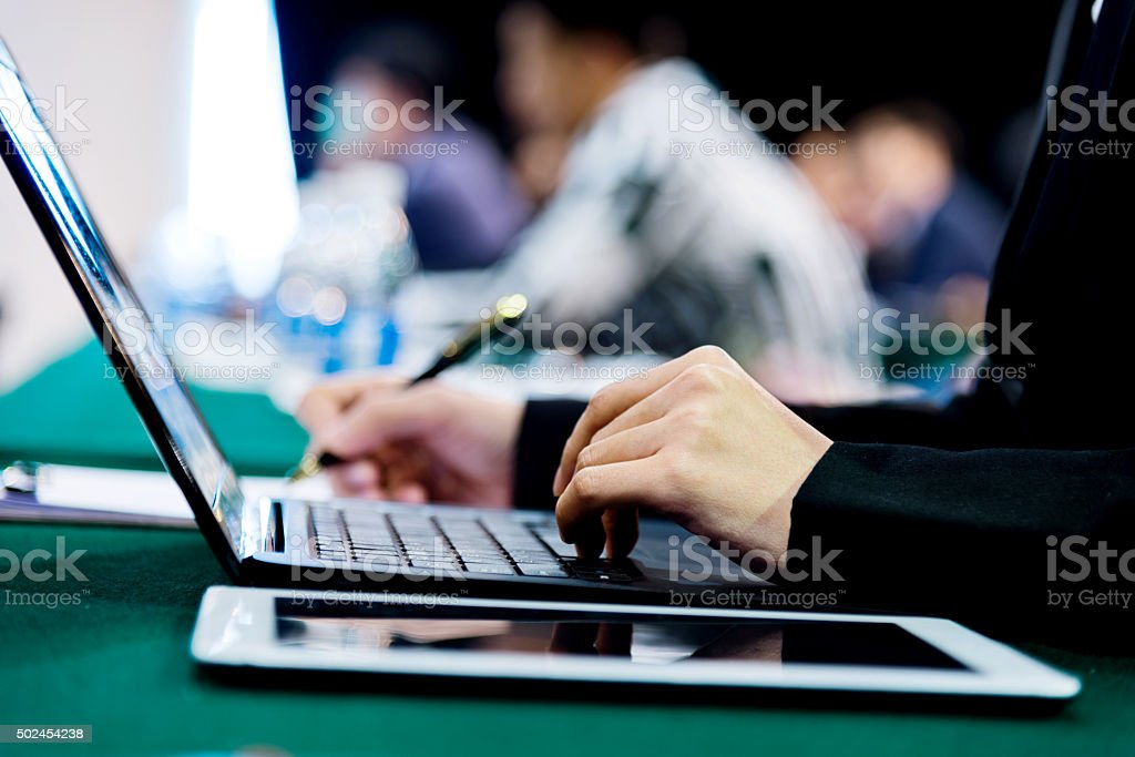 typing on laptop keyboard at conference stock photo