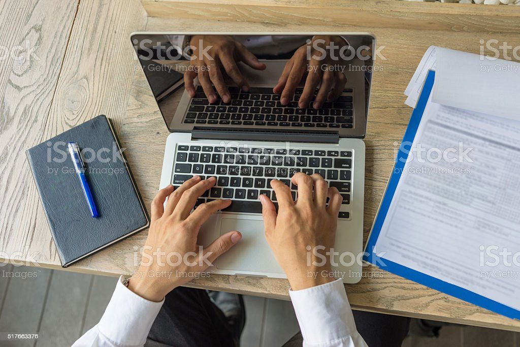 Typing on laptop with document on wooden desk stock photo
