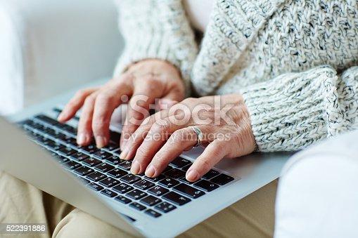Senior female typing on laptop keypad