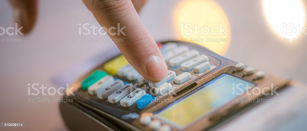 Typing PIN number into a credit card reader stock photo