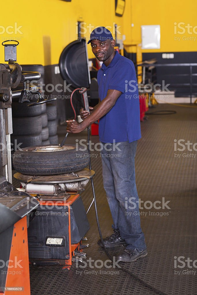 tyre shop worker inflating a trye stock photo