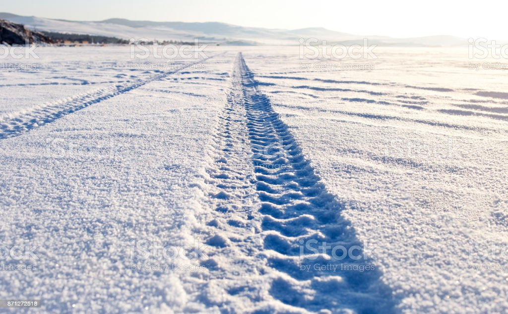 Tyre tracks in the snow on lake Baikal ice surface stock photo