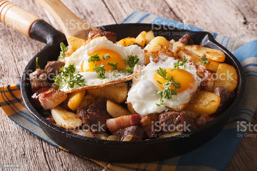 Tyrolean fried potatoes with meat, bacon and eggs in pan stock photo
