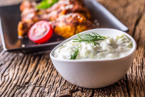Tzatziki. Tzatziki sauce dip or dressing with chicken grill legs in the background stock photo
