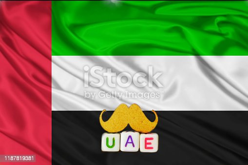 istock uae real texture flag,uae flag and text written UAE on mustaches meaning strong,waving fabric texture of the flag with color of united arab emirates,United Arab Emirates flag 1187819381