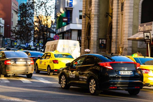 Uber Auto im Verkehr, moderne Stadt Taxi-Service. Autoverschmutzung, Stau am Morgen und Abend in der Hauptstadt Bukarest, Rumänien, 2020 – Foto
