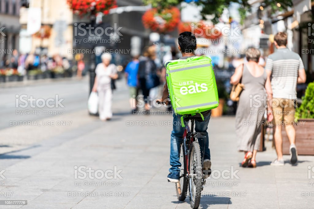Uber eats bicycle man with green sign in old town historic street in capital city during sunny summer day called Krakowskie Przedmiescie stock photo