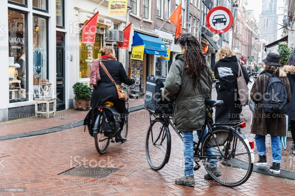 Uber Eats Delivery Man On A Bicycle In Amsterdam Stock Photo