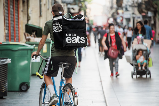 Bordeaux, France. 25 June 2019: A young Uber Eats delivery man moving with a bicycle over St Catherine street, one of the main streets in Bordeaux.