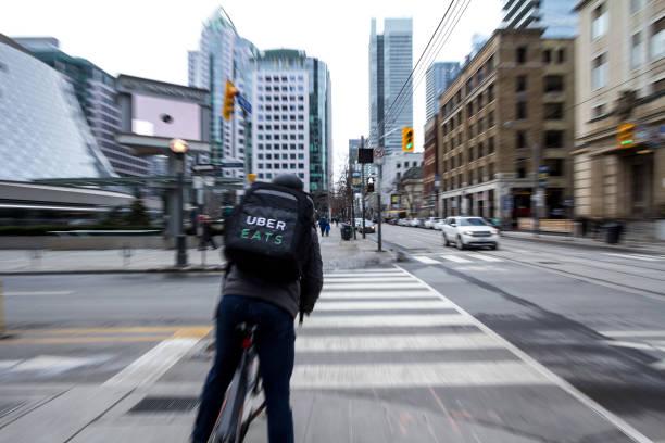 uber isst lieferung mann auf einem fahrrad überqueren eine straße im zentrum von toronto, ontario, mit bewegungsunschärfen warten. uber isst ist einer der marktführer der online-lebensmittel-lieferservice - kinder die schnell arbeiten stock-fotos und bilder