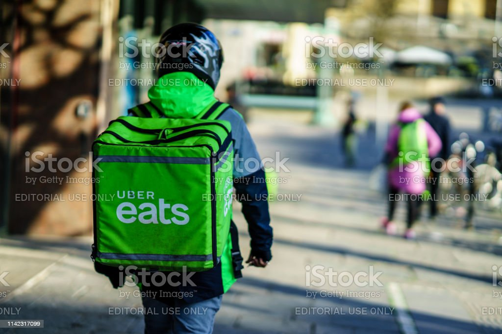 Uber eats delivery person carrying food to people who order by online app Gothenburg, Sweden - April 11, 2019: Uber eats delivery person carrying food to people who order by online app Uber Eats Stock Photo