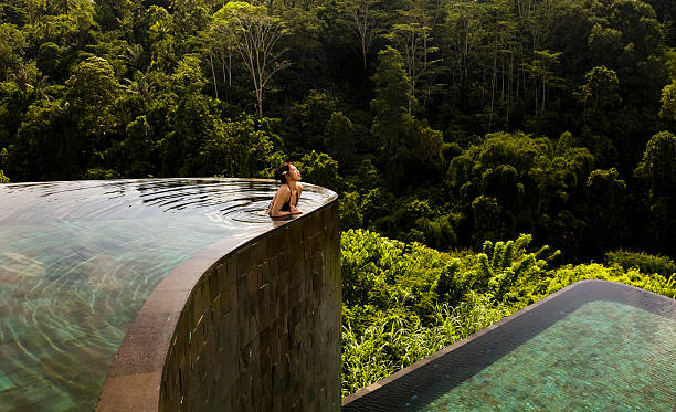 Ubud Hanging Gardens in Bali Indonesia Beautiful setting of a woman leaning over one of two infinity pools at an exotic locale in Ubud, Bali. infinity pool stock pictures, royalty-free photos & images