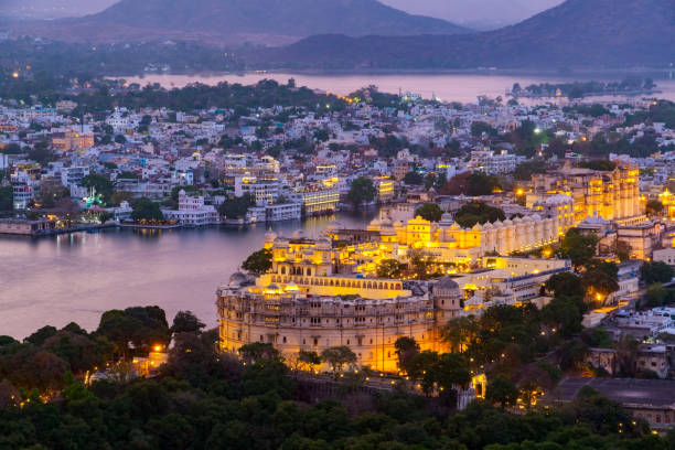 Udaipur city at lake Pichola in the evening, Rajasthan, India. Udaipur city at lake Pichola in the evening, Rajasthan, India. View from  the mountain viewpoint see the whole city reflected on the lake. lake pichola stock pictures, royalty-free photos & images