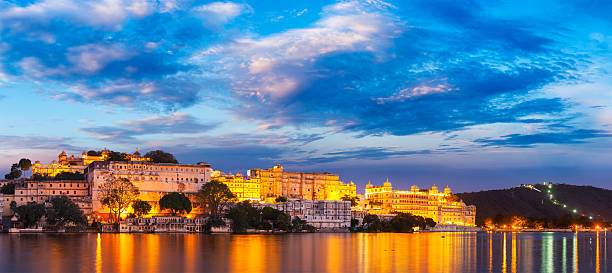 Udaipur City Palace in the evening. Rajasthan, India Panorama of famous romantic luxury Rajasthan indian tourist landmark - Udaipur City Palace in the evening twilight with dramatic sky - panoramic view. Udaipur, India lake pichola stock pictures, royalty-free photos & images