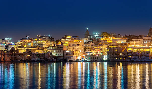 Udaipur Cityscape Lake Pichola Waterfront India Illuminated waterfront of Udaipur, the Lake City or Venice of the East, mirroring in Lake Pichola. Udaipur, Rajasthan, India. lake pichola stock pictures, royalty-free photos & images