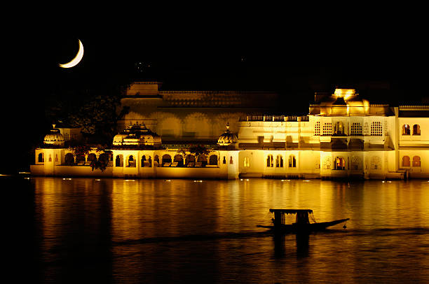 Udaipur Lake Palace at night Udaipur Lake Palace at night with double exposure of the moon lake palace stock pictures, royalty-free photos & images