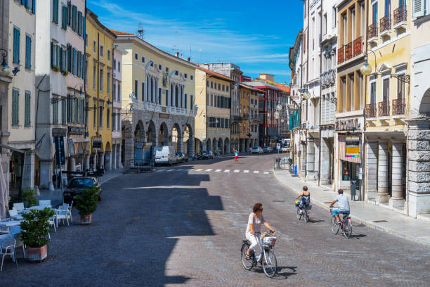 Udine - August of 2013, Friuli Venezia Giulia region, Italy: Street of Udine, people are cycling on the main street of the old city center in sunny summer day stock photo