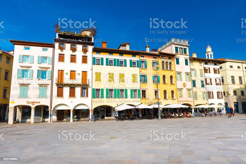 Udine - February of 2017, Italy: View of the central square of Udine (Piazza San Giacomo). Colored residential houses in the traditional architecture style against the clear blue sky stock photo