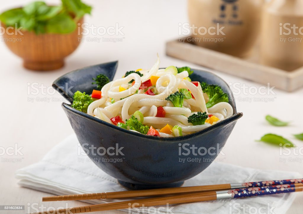 Udon, Japanese noodles with vegetables in a handmade ceramic bow stock photo