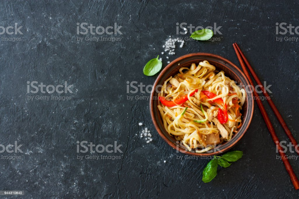 Udon noodles and vegetables served in the clay pot stock photo
