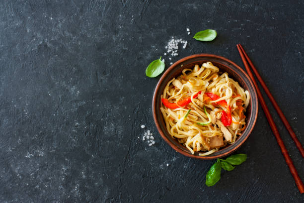 Udon noodles and vegetables served in the clay pot Udon noodles and vegetables served in the clay pot on a black stone background asian food stock pictures, royalty-free photos & images