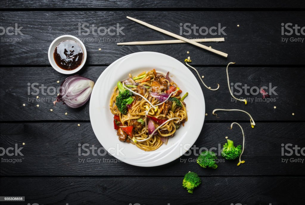 Udon stir fry noodles with meat or chicken and vegetables in a white plate with chopsticks. stock photo