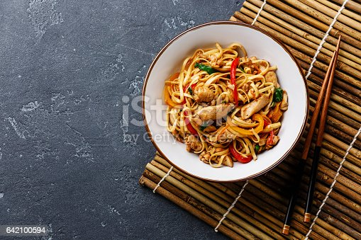 Udon stir-fry noodles with chicken in bowl on dark stone background copy space
