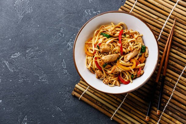 Udon stir-fry noodles with chicken in bowl Udon stir-fry noodles with chicken in bowl on dark stone background copy space asian food stock pictures, royalty-free photos & images