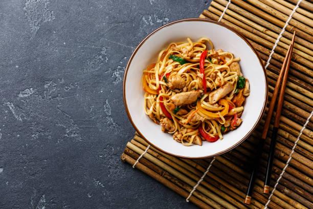 udon stir-fry noodles with chicken in bowl - thai food stockfoto's en -beelden